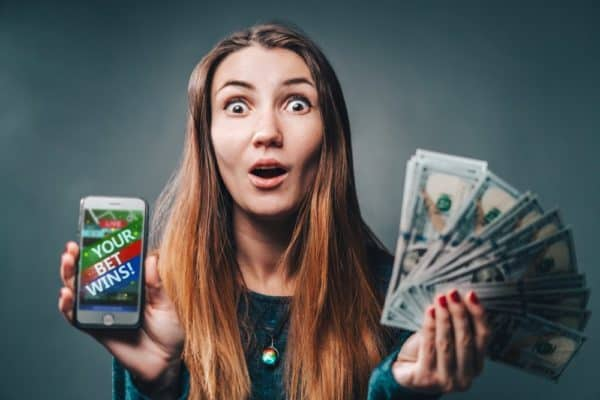 woman being happy winning a bet using a sports betting app on her phone