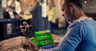 man using online sports betting services on his phone and laptop
